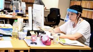 Frau vor Computer mit Schutzschirm vor dem Gesicht