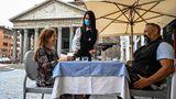 Ein Kellner serviert zwei Gästenauf einer Café-Terrasse am Pantheonim Zentrum Roms Kaffee.In Italien dürfen sich die Menschen seit Montaginnerhalb ihrer Region wieder frei bewegen. Auch Restaurants, Bars, Friseursalons, Geschäfte und Museen öffnen wieder.