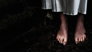 Füße auf dunklem Waldboden