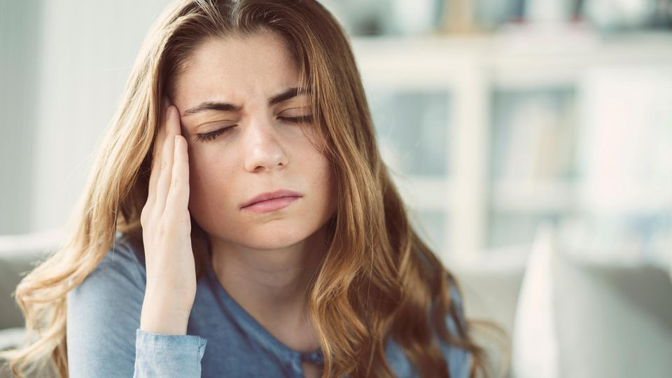 Eine Frau hält sich vor Schmerzen die Schläfe