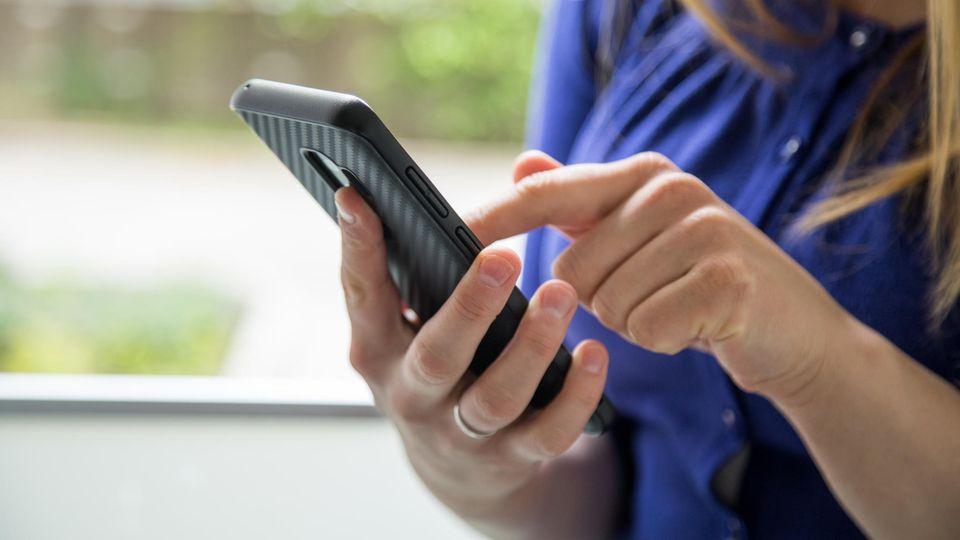 Frau bedient Smartphone - Nummer unterdrücken