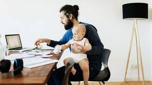Mann sitzt vor Laptop mit Baby auf dem Schoß