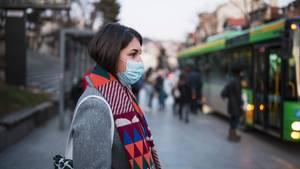 Coronavirus: Eine Frau mit Maske steigt in einen Bus