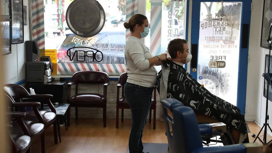Eine Friseurin schneidet einem Mann die Haare