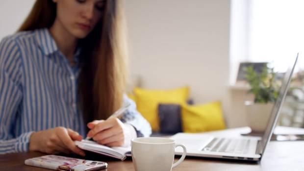 Eine langhaarige Frau sitzt an einem Schreibtisch mit Laptop und notiert sich etwas in einen Kalender