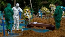 """Friedhofsmitarbeiter in Schutzanzügen begraben einen Toten auf dem Friedhof """"Nossa Senhora Aparecida"""" in Manaus"""