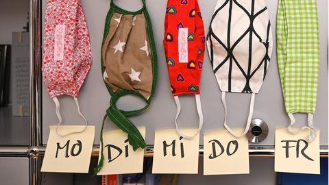 Selbstgenähte Mund- und Nasenmasken aus Stoff hängen in einem Büro an einem Aktenschrank