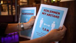 Zettel mit Hygienevorschriften werden in einem Restaurant aufgehängt