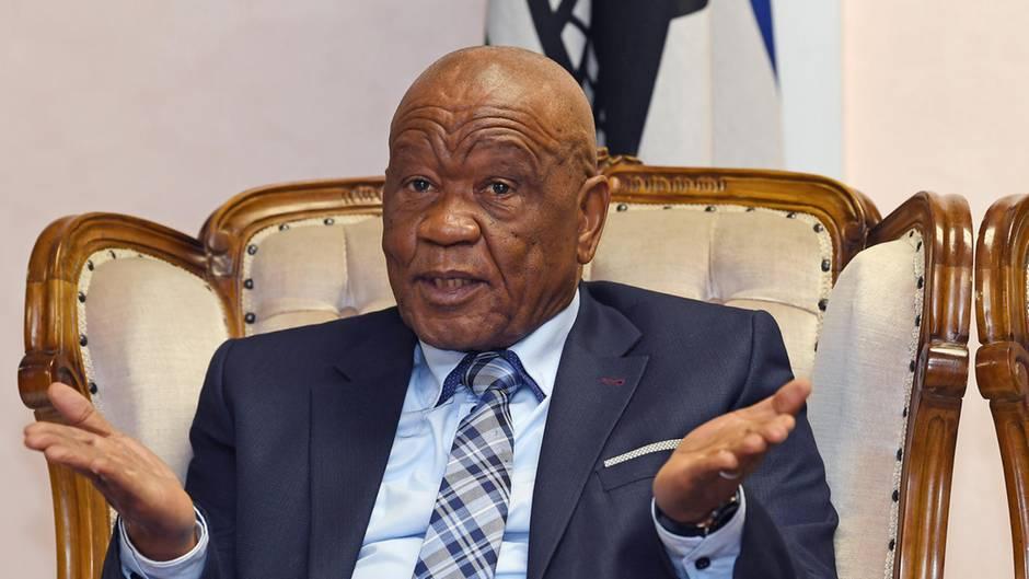 Ein afrikanischer Mann sitzt im Anzug in einem Ohrensessel mit weißem Bezug