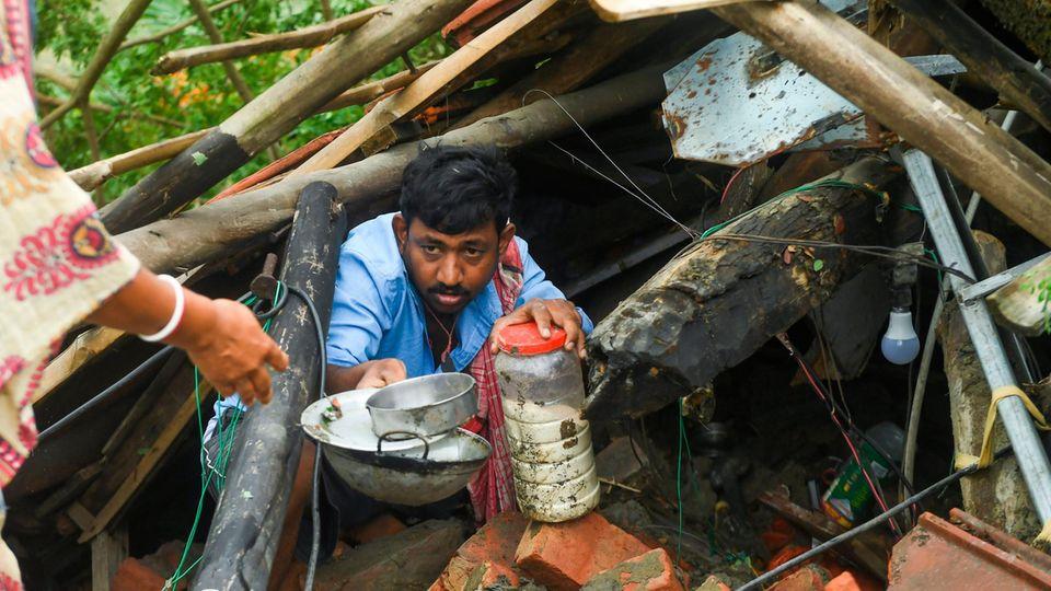 Ein Mann rettet Habseligkeiten aus seiner zerstörten Behausung in Mindapur, Westbengalen