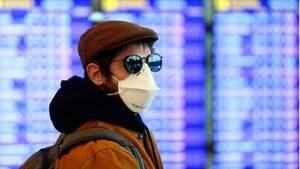 Ein Mann mit einer Schutzmaske am Flughafen von Barcelona