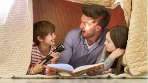 Vater und zwei Kinder mit Taschenlampe beim Buch vorlesen unter einer Decke