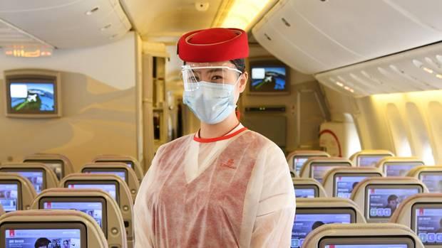 Fliegen zu Corona-Zeiten: Eine Flugbegleiterin an Bord eines Jets vom Emirates Airlines