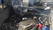 Feuerwehrleute löschen an der Absturzstelle in einem Wohngebiet in Karatschi
