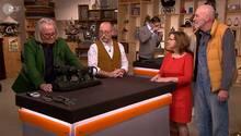 """""""Bares für Rares""""-Experte Albert Maier begutachtet die Figur vonHeinz Schulze und Marita Schreven. Moderator Horst Lichter (Mitte) schaut zu."""