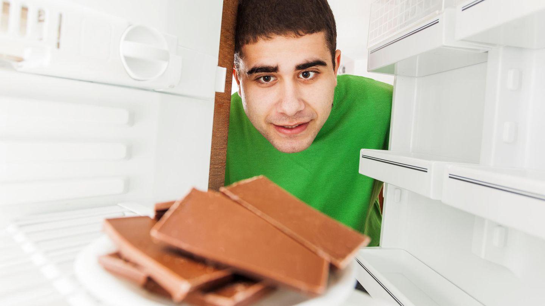 Ein Mann schaut in einen Kühlschrank, in dem Schokolade liegt.