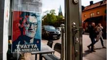 Ein Schild mit einem Porträt von Anders Tegnell hängt am Eingang eines Restaurants in Stockholm