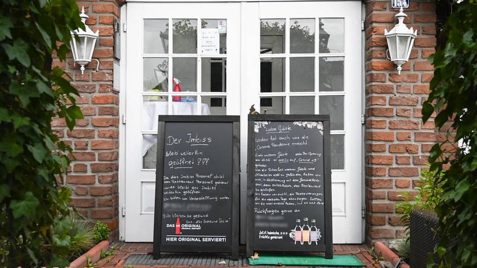 Vor der weißen Flügeltür in ein Backstein-Gebäude stehen zwei Tafeln, auf denen denen das Restaurant auf Corona-Fälle hinweist