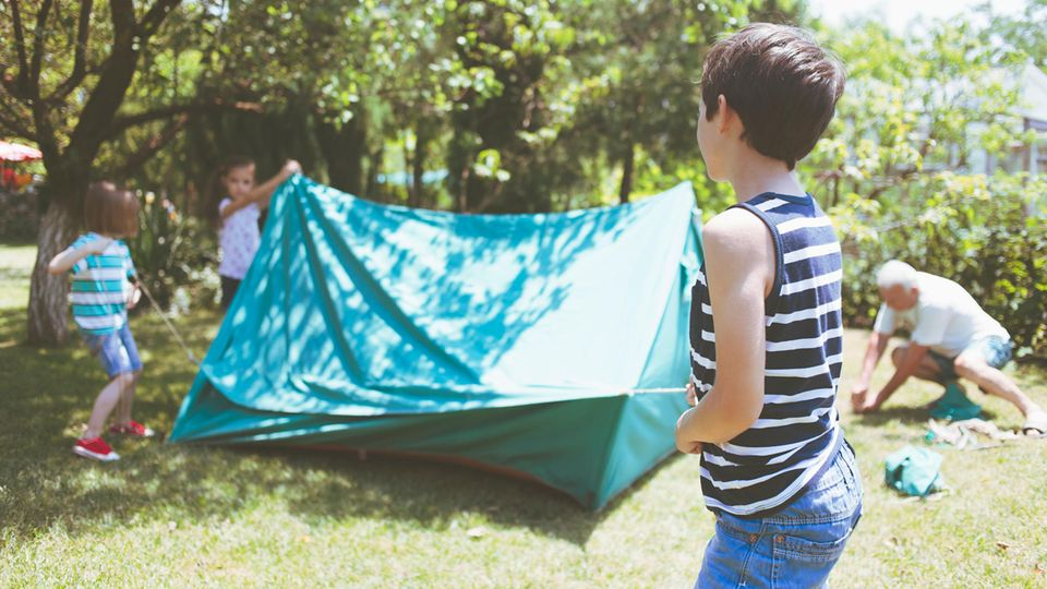 Kinder bauen ein Zelt auf