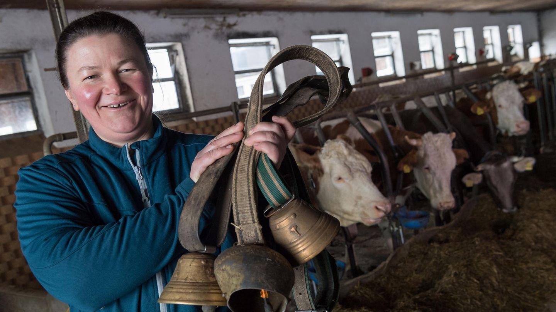 Milchbäuerin mit ein paar Kuhglocken in der Hand