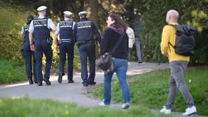 Vier Polizisten laufen durch einen Park gefolgt von Fußgängern