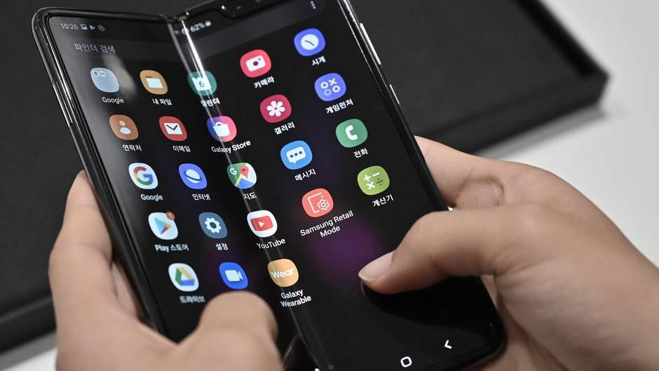 Zwei Hände halten ein Smartphone mit faltbarem Display