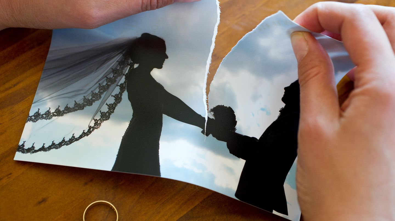 Hände zerreißen ein Hochzeitsfoto