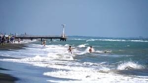 Besucher schwimmen am Strand von Ostia im Meer