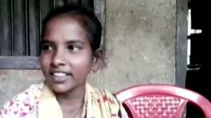 Auf einem roten Plastikstuhl sitzt ein indisches Mädchen mit zurückgebundenen Haaren und einem geblümten Oberteil