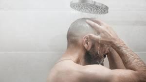 Ein Mann steht unter der Dusche