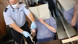 Moers: Dem Angeklagten Bastian S. (r) werden von einem Justizbeamten im Gerichtssaal die Handschellen abgenommen