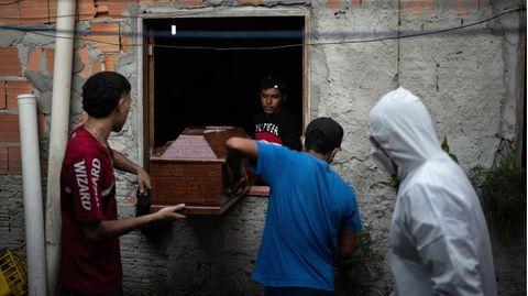 In Manaus heben Verwandte einen Sarg mit einem mutmaßlichen Corona-Opfer durch ein Fenster nach draußen