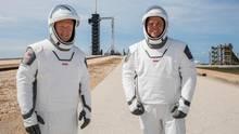 US-Astronauten Douglas Hurley und Robert Behnken mit Falcon-9-Rakete im Hintergrund