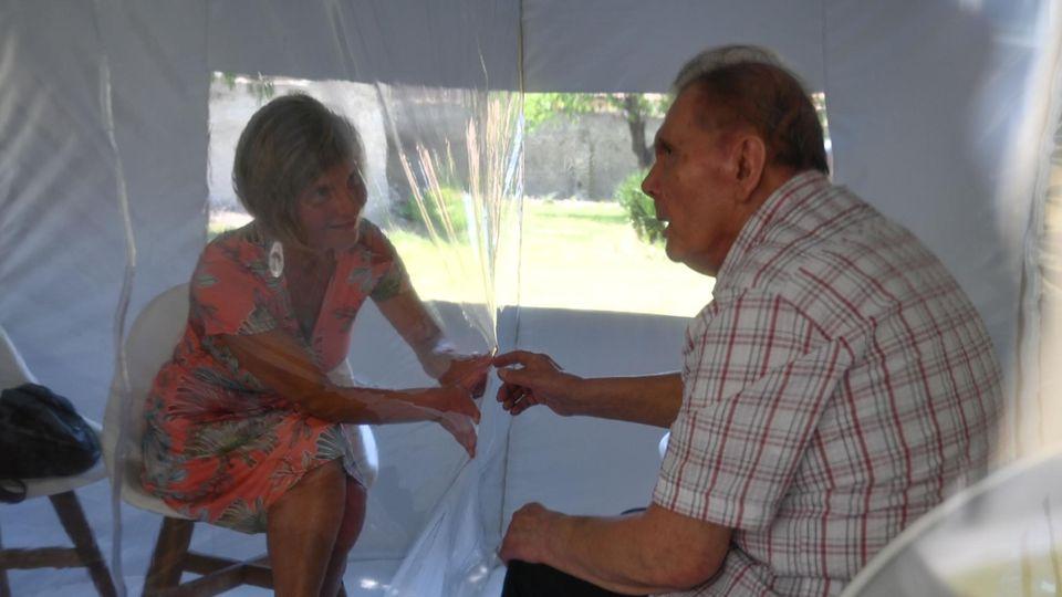 Ein Ehepaar im Bubble Tent, sie hält durch die Folie seine Hand