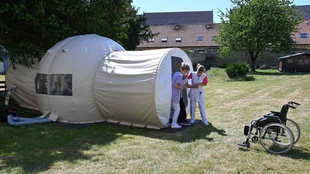 Betreuerinnen helfen einem Bewohner aus dem Zelt