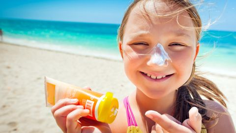 Ökotest Sonnencreme für Kinder im Test: Ein Mädchen benutzt eine Sonnencreme