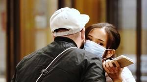 Begrüßung eines Paares mit Atemschutzmasken