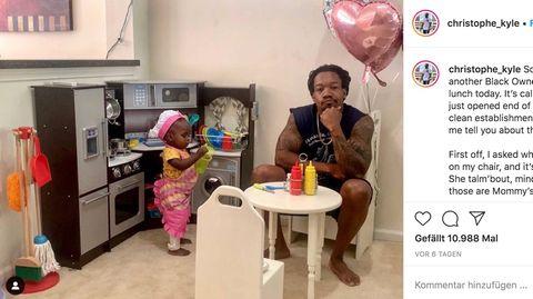 Der Vater Christophe Kyle sitzt an dem kleinen Tisch des Fantasie-Restaurants, neben ihm steht seine kleine Tochter mit Schürze