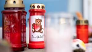 Grablichter mit gemalten Teddys stehen auf dem Boden