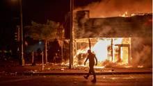 Ein Mann steht in der Nacht vor einem brennenden Gebäude