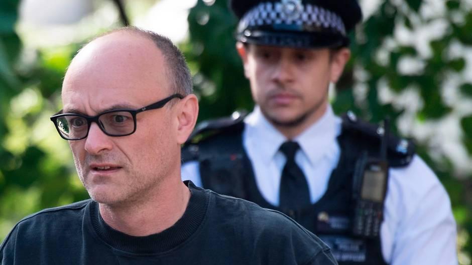 Ein Mann mit schwarzer Hornbrille und rasierten Haaren geht im schwarzen Basketball-Shirt an einem britischen Polizisten vorbei