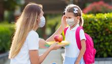Schulkind und Mutter mit Mundschutzen