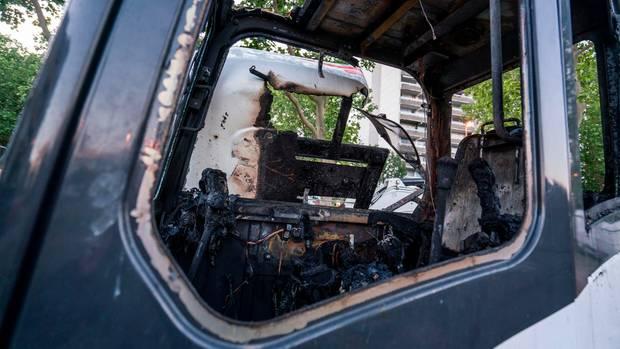 Ein ausgebrannter Bagger steht am Rande einer Hochhaussiedlung