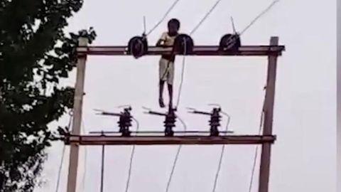 Ein Junge aus Nordindien klettert auf einen acht Meter hohen Strommast