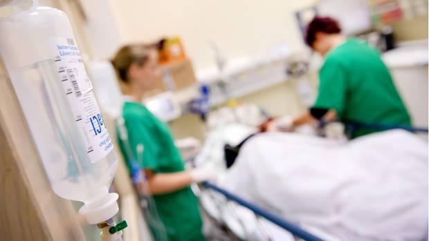 Medizinisches Personal versorgt in einem Krankenhaus einen Patienten.