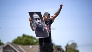 Demonstrant hält in Minneapoliseinen Zettel mit dem Porträt von George Floyd in die Höhe