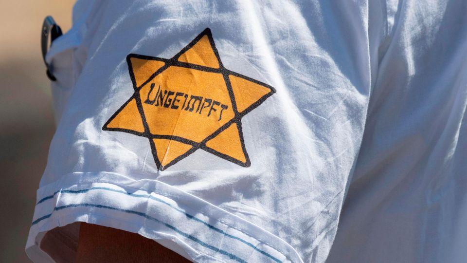 """""""Ungeimpft"""" steht auf einem nachgebildeten Judenstern am Arm eines Mannes auf einer Demonstration in Frankfurt am Main"""