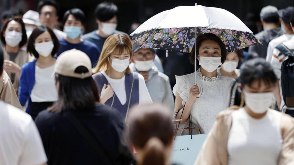 Zahlreiche Passanten mit Mundschutz gehen in Osaka, Japan auf einer Straße