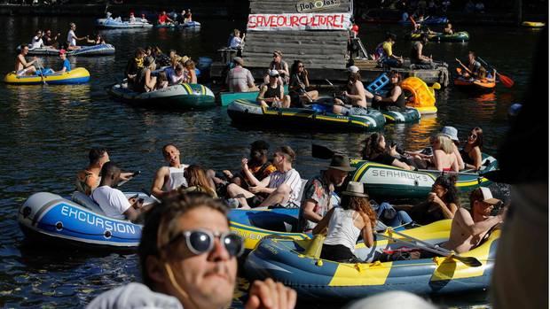 Auf dem Landwehrkanal in Berlin treiben bei Sonnenschein viele vollbesetzte Schlauchboote