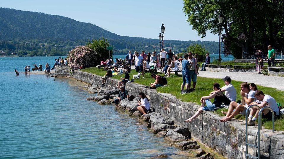 Zahlreiche Ausflügler genießen das schöne Wetter am Ufer des Tegernsees in Bayern